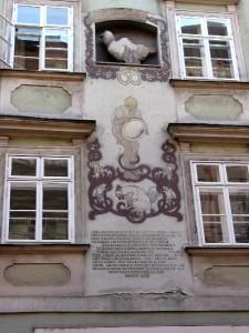 Фасад дома №7 - фреска и памятная надпись. Сверху камень, символизирующий окаменелого василиска, вылупившегося из яйца.